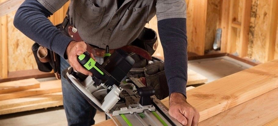 Man using power saw on a wooden board 2